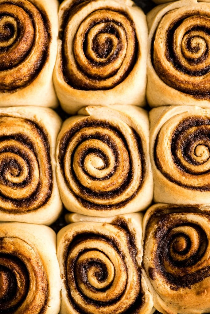 overhead view of a pan of 12 baked cinnamon rolls before being frosted in the making of this cinnamon roll recipe
