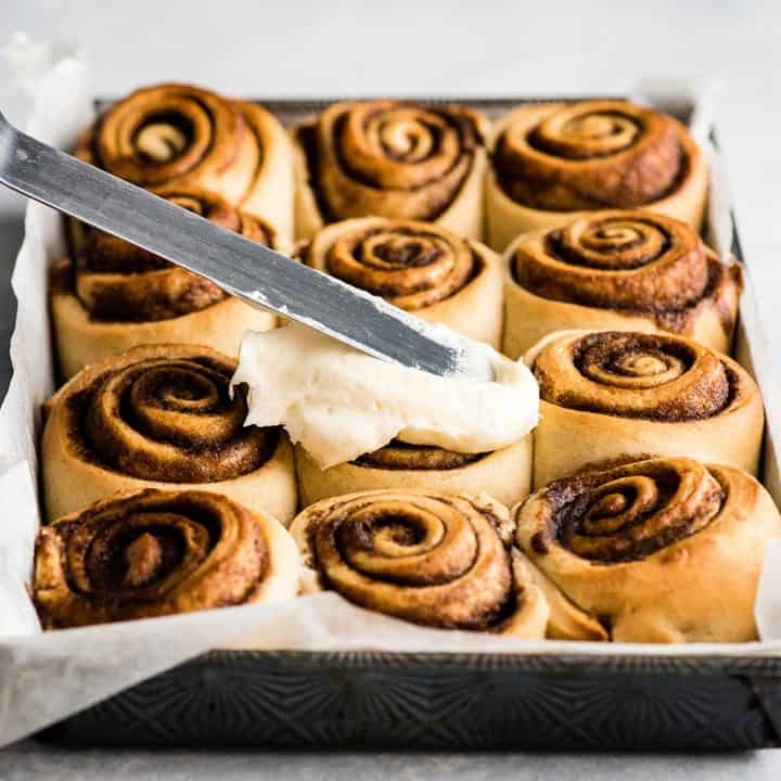 front view of cinnamon rolls being frosted with cream cheese frosting