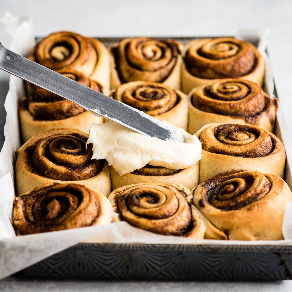 front view of this cinnamon roll recipe being frosted with cream cheese frosting.