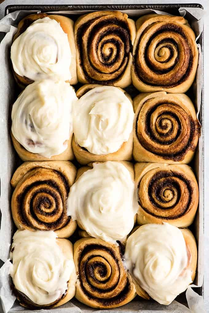 Overhead view of a pan of the best cinnamon rolls recipe after baking, with six cinnamon rolls frosted and six unfrosted