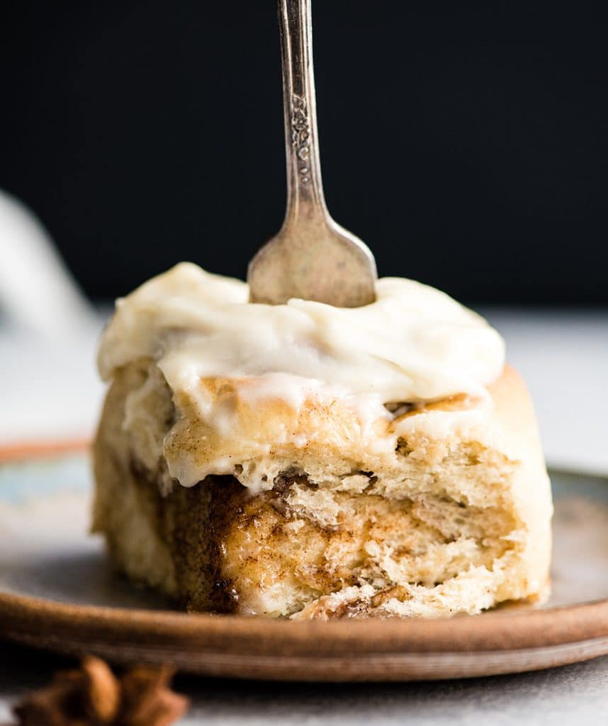 front view of a Best Cinnamon Roll recipe on a plate with a fork in it ready to take a bite