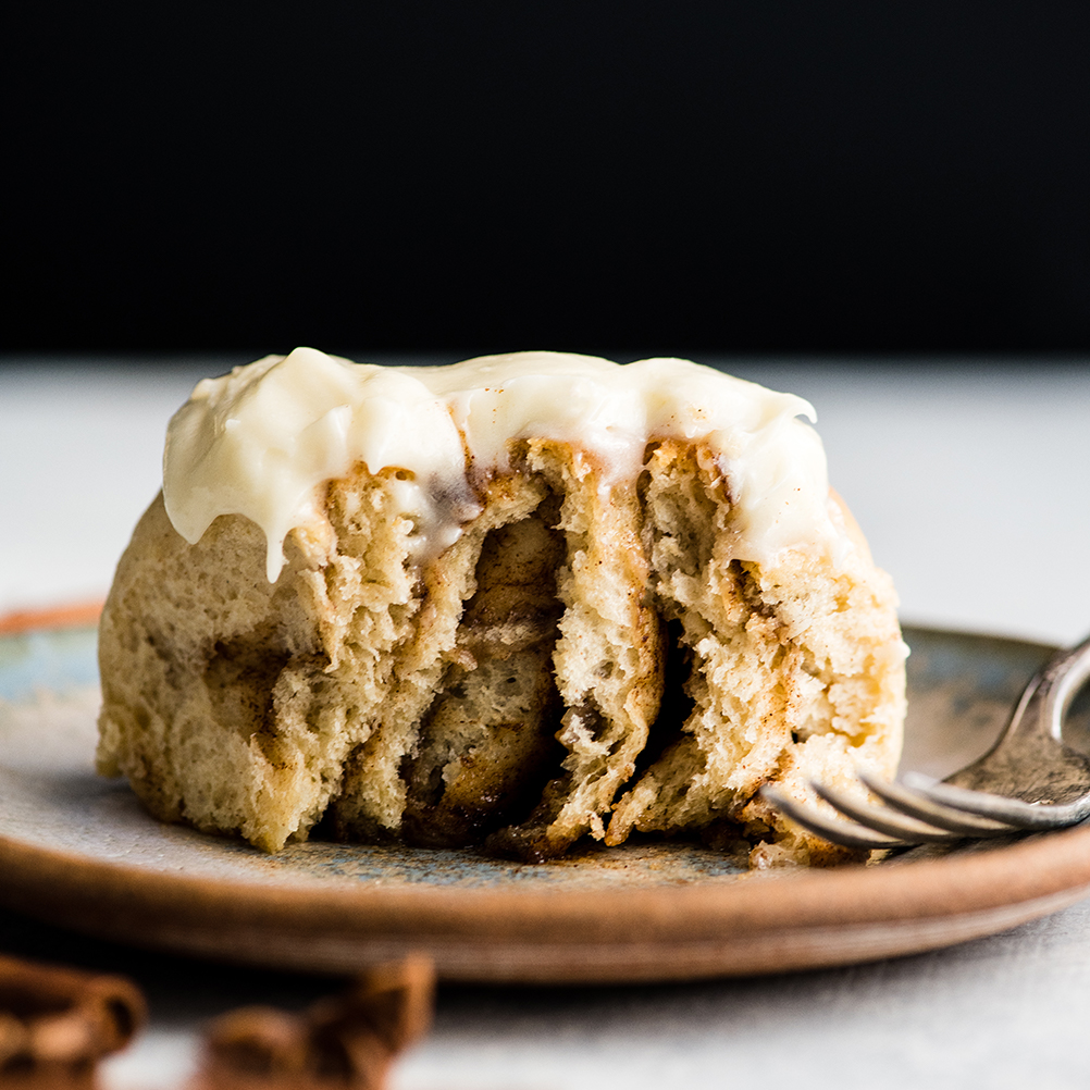 front view of a frosted cinnamon roll on a plate after a bite has been taken showing the swirly gooey insides of this cinnamon roll recipe