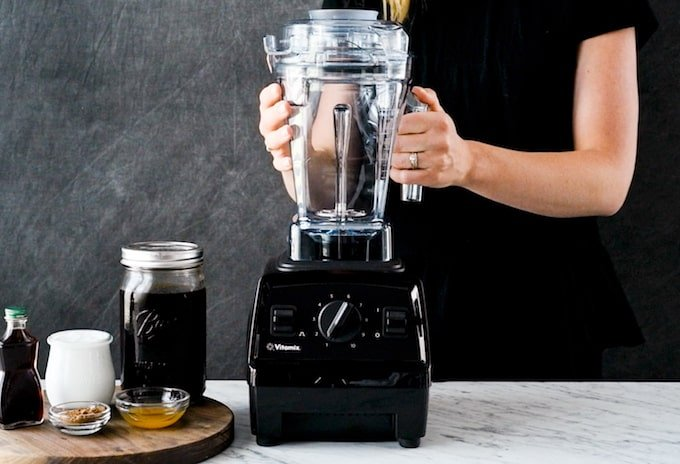 Front view of a person blending in a Vitamix Explorian 310 blender in this post answering the question Which Vitamix is the Best? (Vitamix Comparison & Buying Guide)