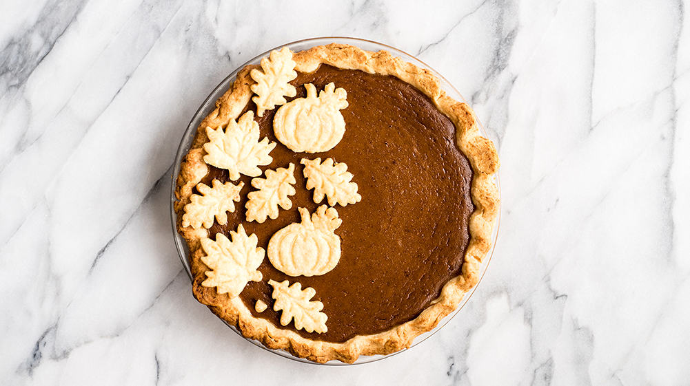 overhead view of a pumpkin pie with Flaky Homemade All Butter Pie Crust shapes on top and crust on the sides