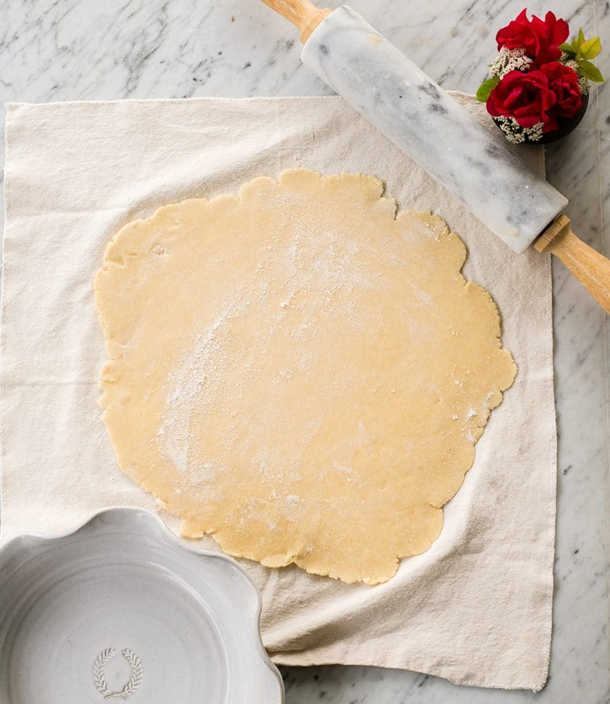 overhead view of a Flaky Homemade All Butter Pie Crust rolled out on a pastry cloth