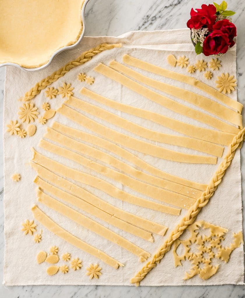 overhead view of Flaky Homemade All Butter Pie Crust cut into shape, long strips and braided to be used for the top of the pie