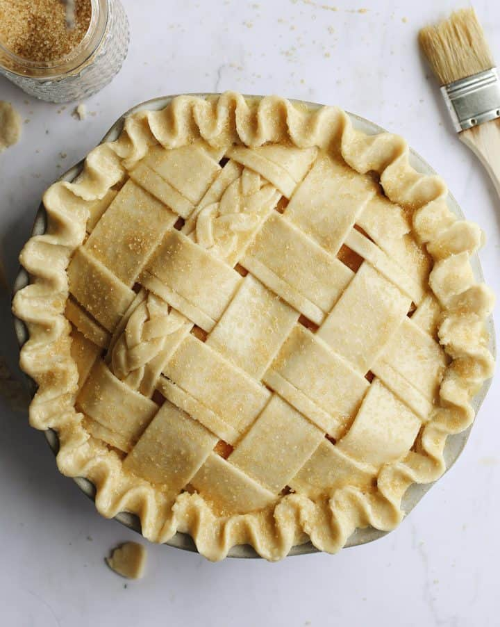 overhead photo of a Butter Pie Crust in a lattice pattern before baking with an egg wash and raw sugar