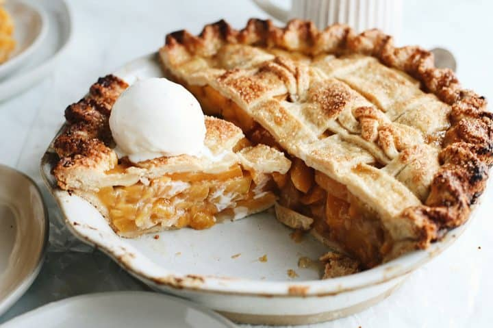 front view of a peach pie with a double Butter Pie Crust with a slice cut out and ice cream on top