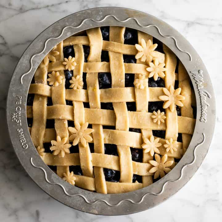 overhead view of an unbaked pie with a pie crust shield protecting the outer Pie Crust
