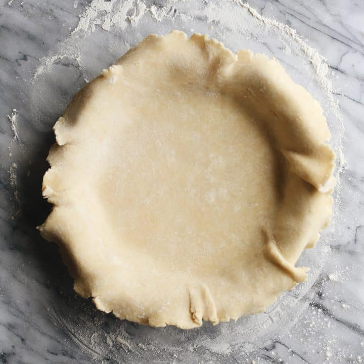 a butter pie crust in a pie plate before baking