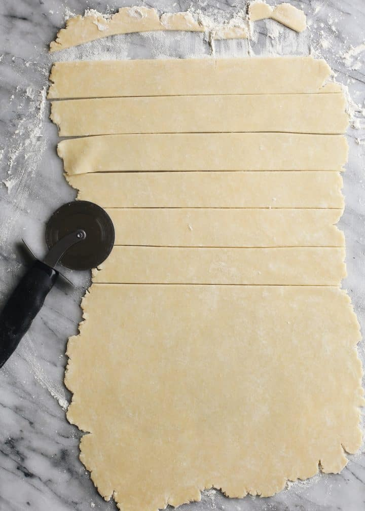 butter pie crust rolled out and being cut to make a lattice top