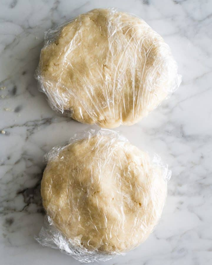 two discs of How to butter Pie Crust wrapped in plastic wrap to chill
