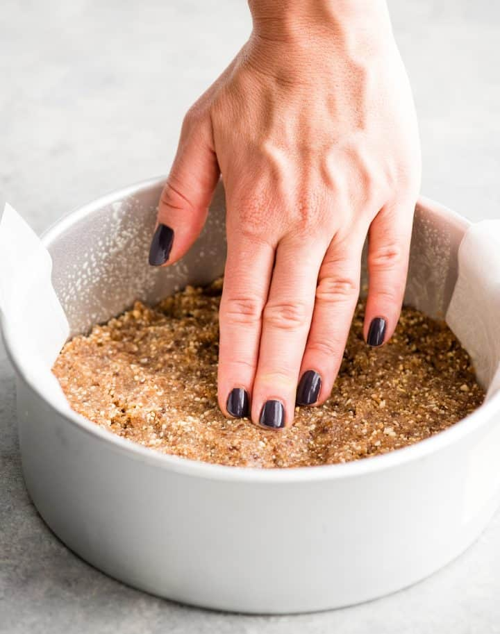 front view of a hand pressing the crust of this No-Bake Vegan Pumpkin Cheesecake recipe down into the cake pan so it is flat and even.