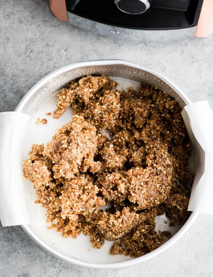 overhead view of a cake pan lined with parchment paper after the crust ingredients for this No-Bake Vegan Pumpkin Cheesecake have been poured into it