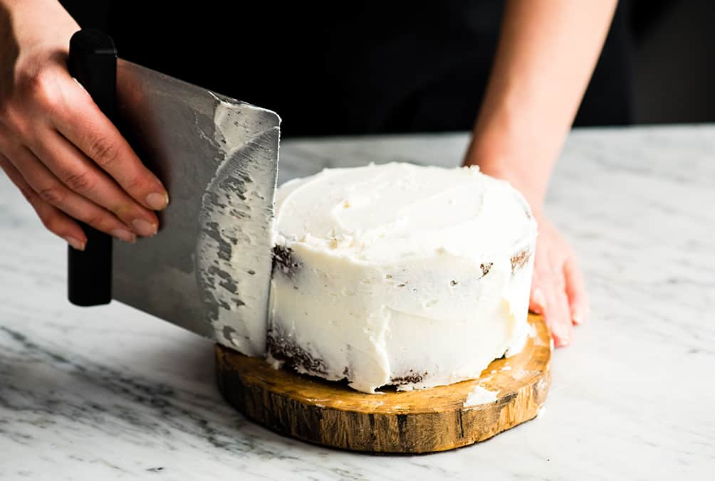 "Front view of a person frosting a 6"" round cake with white frosting to make a Birthday Cake for Jesus"