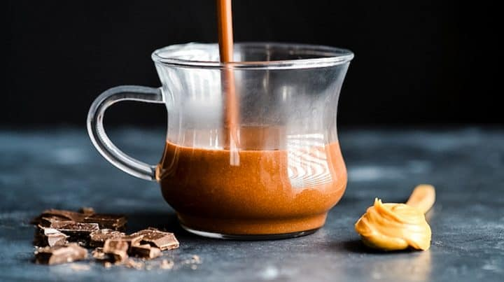 Peanut Butter Hot Chocolate being poured into a glass mug