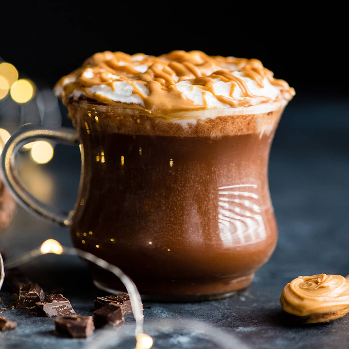 a glass mug filled with Peanut Butter Hot Chocolate topped with whipped cream and a drizzle of peanut butter