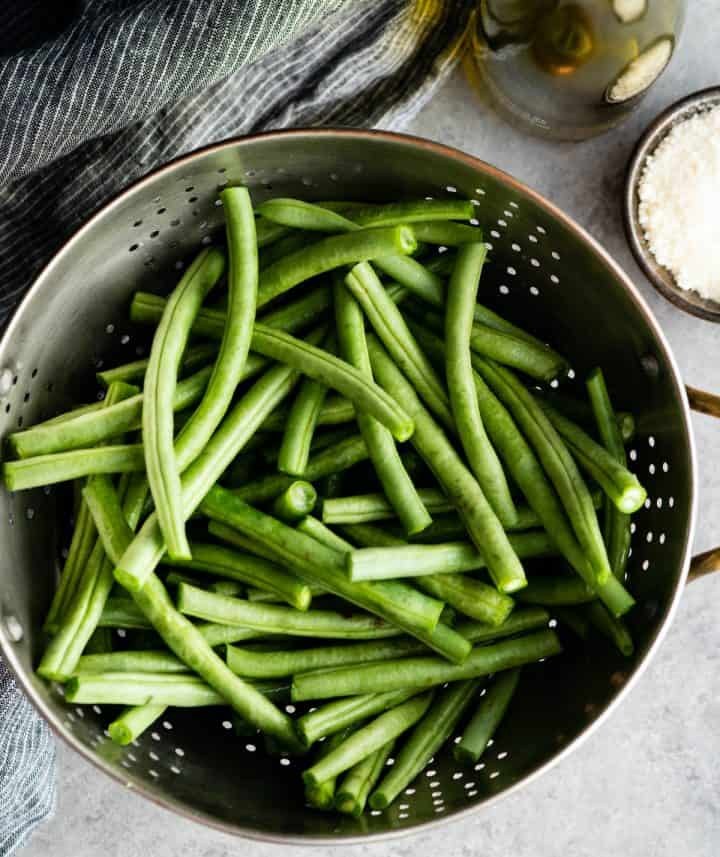 overhead view of fresh green beans in a colander with the other ingredients around it needed to make this Roasted Parmesan Green Beans recipe