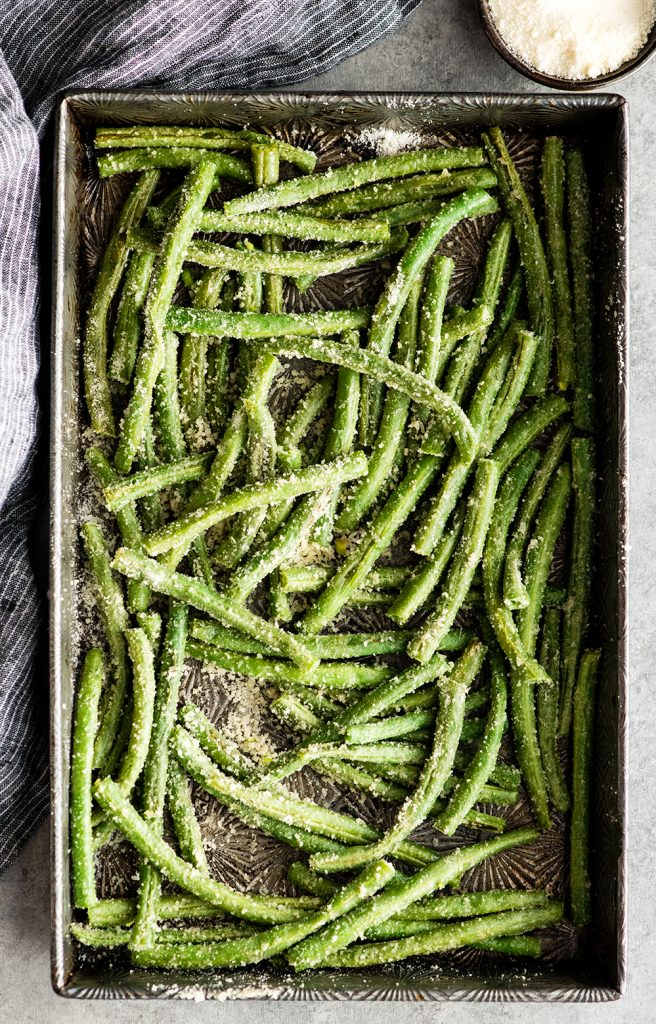 overhead view of green beans in a baking pan coated with parmesan cheese before baking in the making of this Roasted Parmesan Green Beans recipe