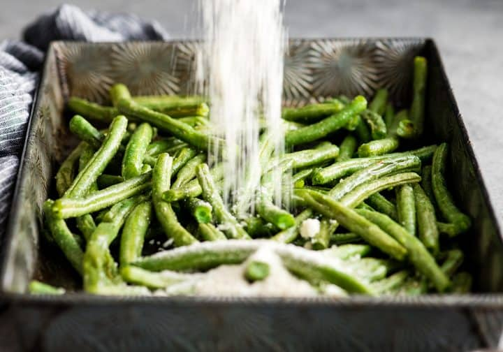 front view of parmesan cheese being poured onto green beans in a baking sheet in the making of this Roasted Parmesan Green Beans recipe