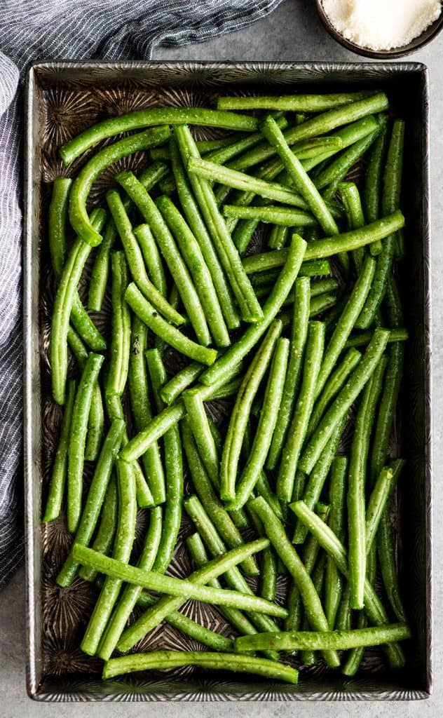 overhead view of a baking sheet with green beans tossed with olive oil and spices in the making of this Roasted Parmesan Green Beans recipe