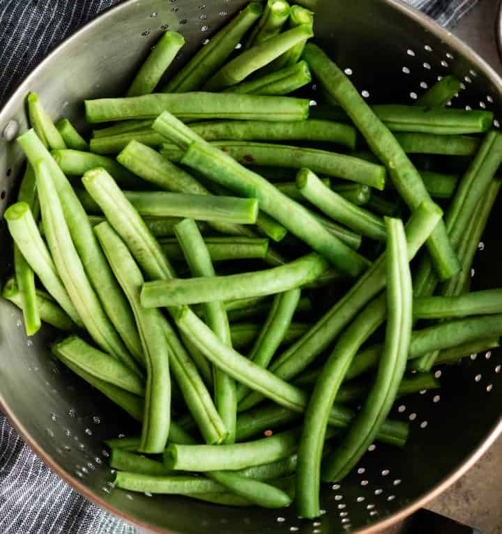 overhead photo of fresh green beans in a colander to be washed