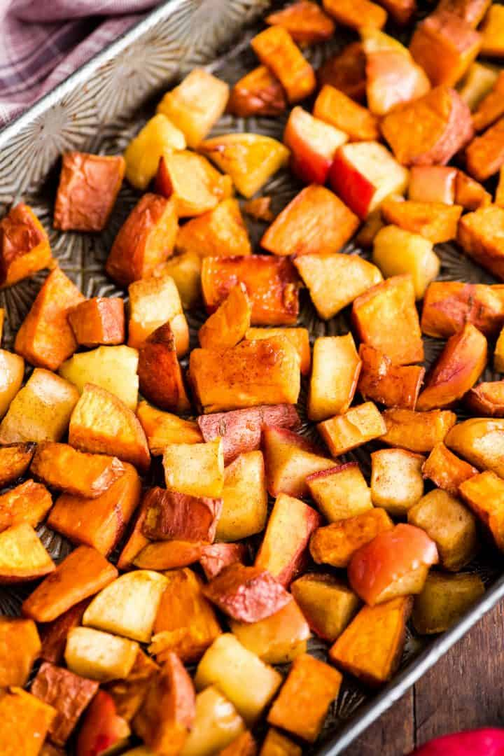 Overhead view of Cinnamon Roasted Sweet Potatoes and Apples on a baking sheet after being roasted