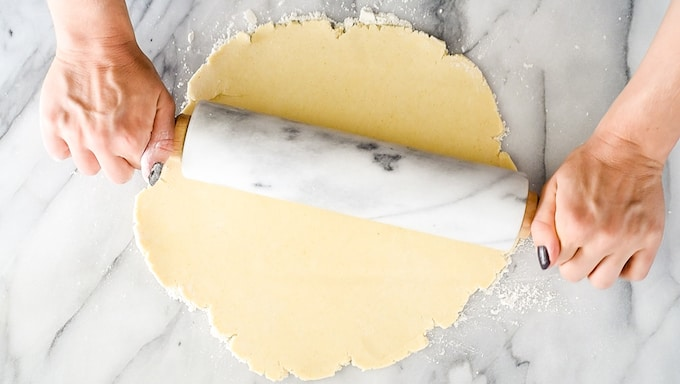 Overhead view of two hands rolling out a pie crust, Moments November 2018