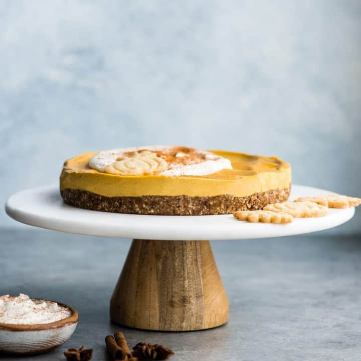 Front view of a full No-Bake Vegan Pumpkin Cheesecake on a cake stand topped with whipped cream and a sprinkle of cinnamon