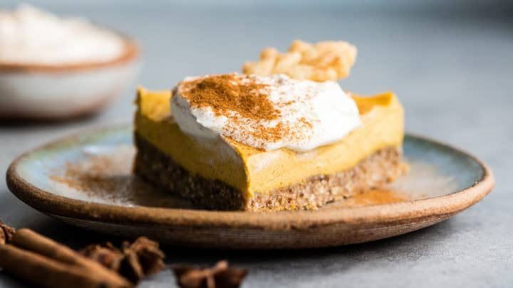front view of a piece of Vegan Pumpkin Cheesecake on a plate topped with whipped cream and cinnamon