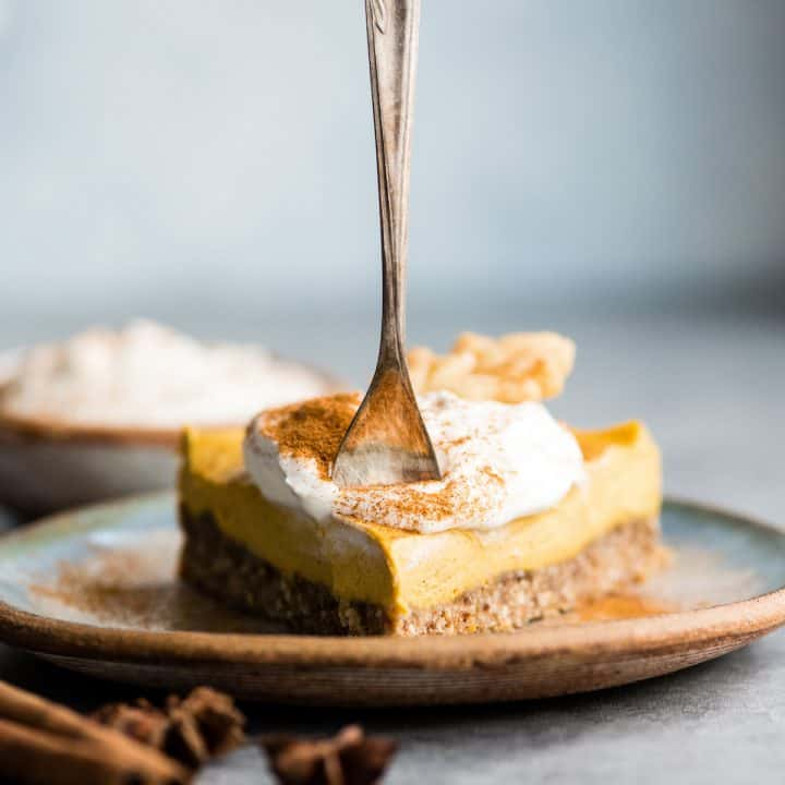 front view of a slice of No-Bake Vegan Pumpkin Cheesecake on a plate with a fork in it ready to take a bit
