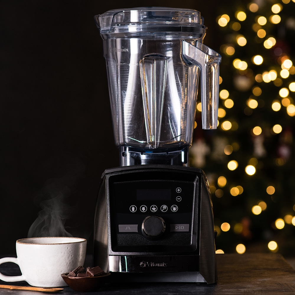 Front view of a Vitamix A3500 Blender with a warm cup of cocoa next to it and a Christmas tree in the background, Moments November 2018