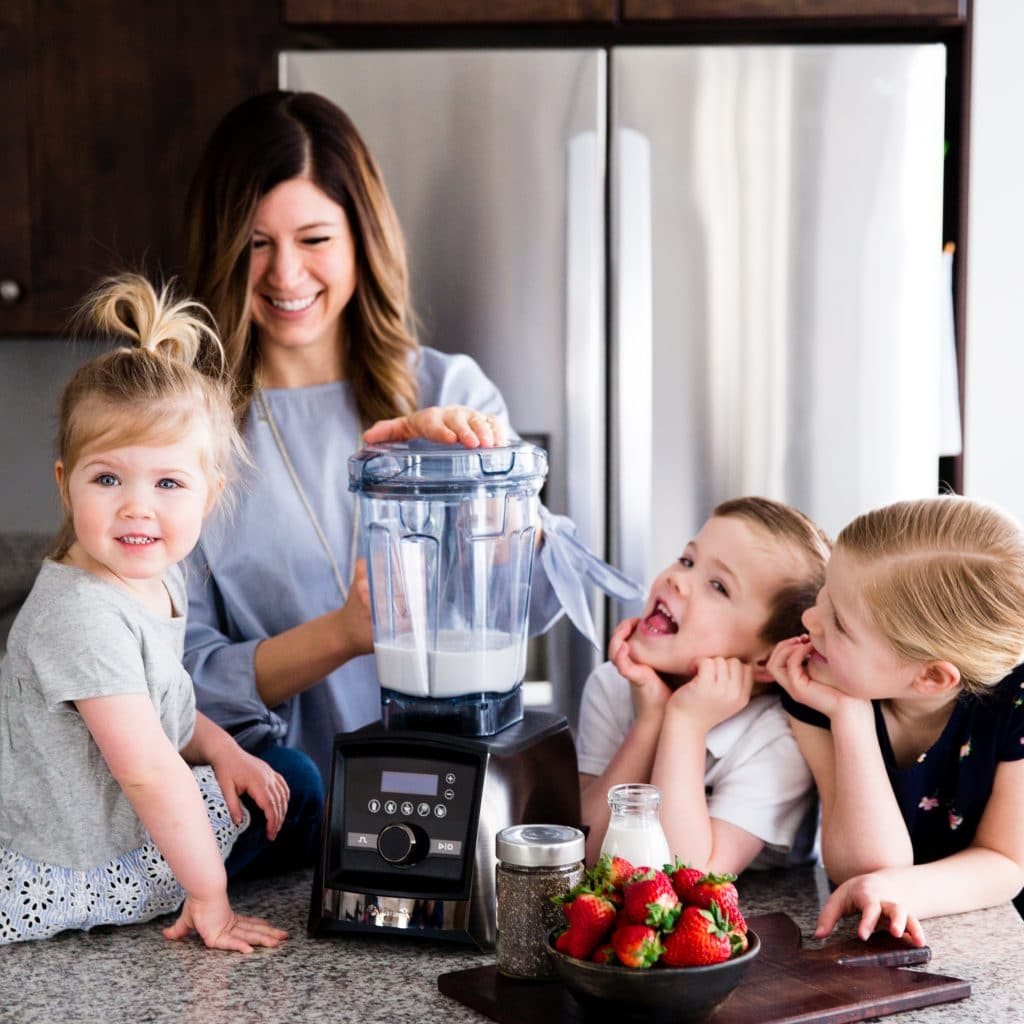 Front view of a mom and her kids blending in the Vitamix A3500 blender in this post answering the question Which Vitamix is the Best? (Vitamix Comparison & Buying Guide)