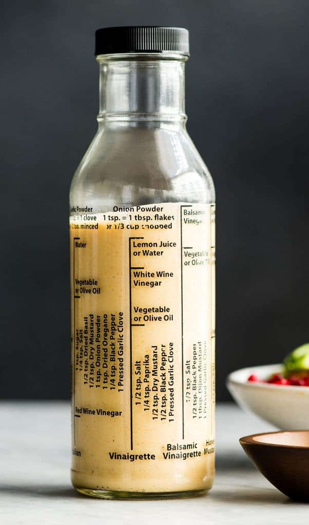 front view of a glass bottle filled with Apple Cider Vinaigrette dressing