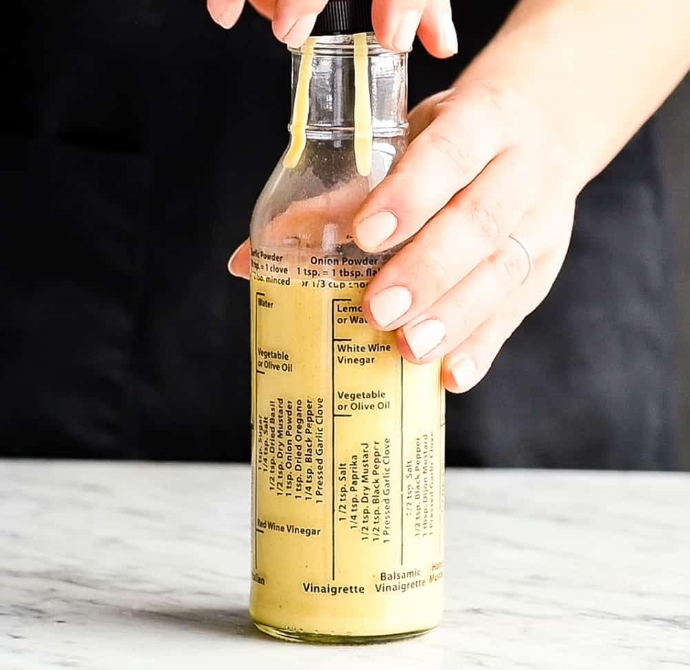Front view of a hand putting the lid on a bottle of homemade Apple Cider Vinaigrette dressing