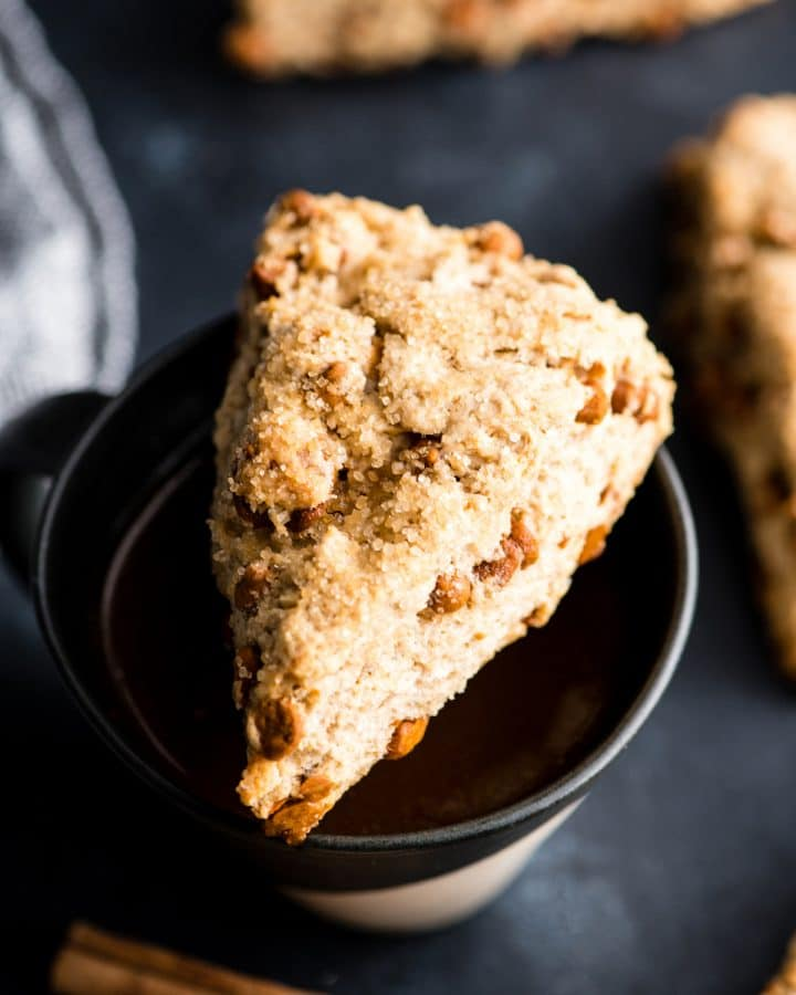 Overhead view of a Cinnamon Scone (with Cinnamon Chips) resting on a cup of coffee, with other scones around it