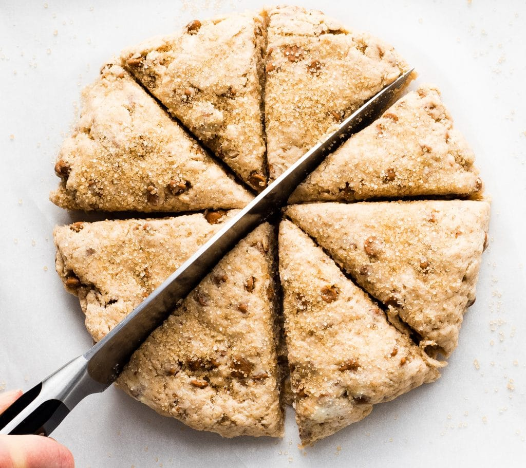 overhead view of a hand holding a knife cutting a circle of cinnamon chip scone dough into eight pieces.