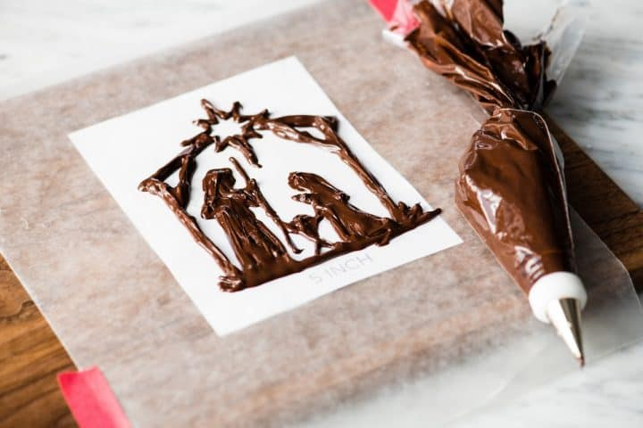 front/side view of a nativity scene cake topper fully traced with chocolate in the making of this Birthday Cake for Jesus
