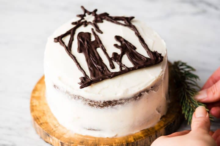nativity cake on a wooden circle with hands situation pine branches around it