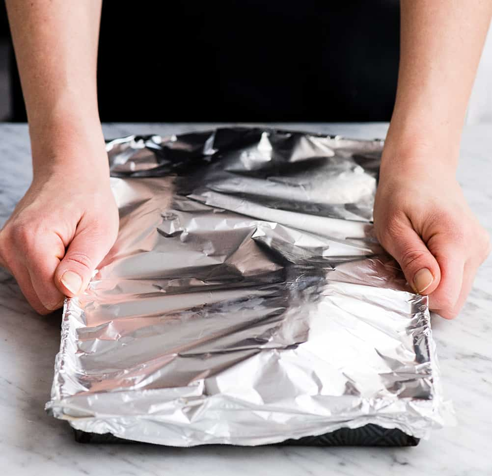 front view of hands placing aluminum foil over a baking sheet before placing it in the oven to make Spaghetti Squash Mac and Cheese