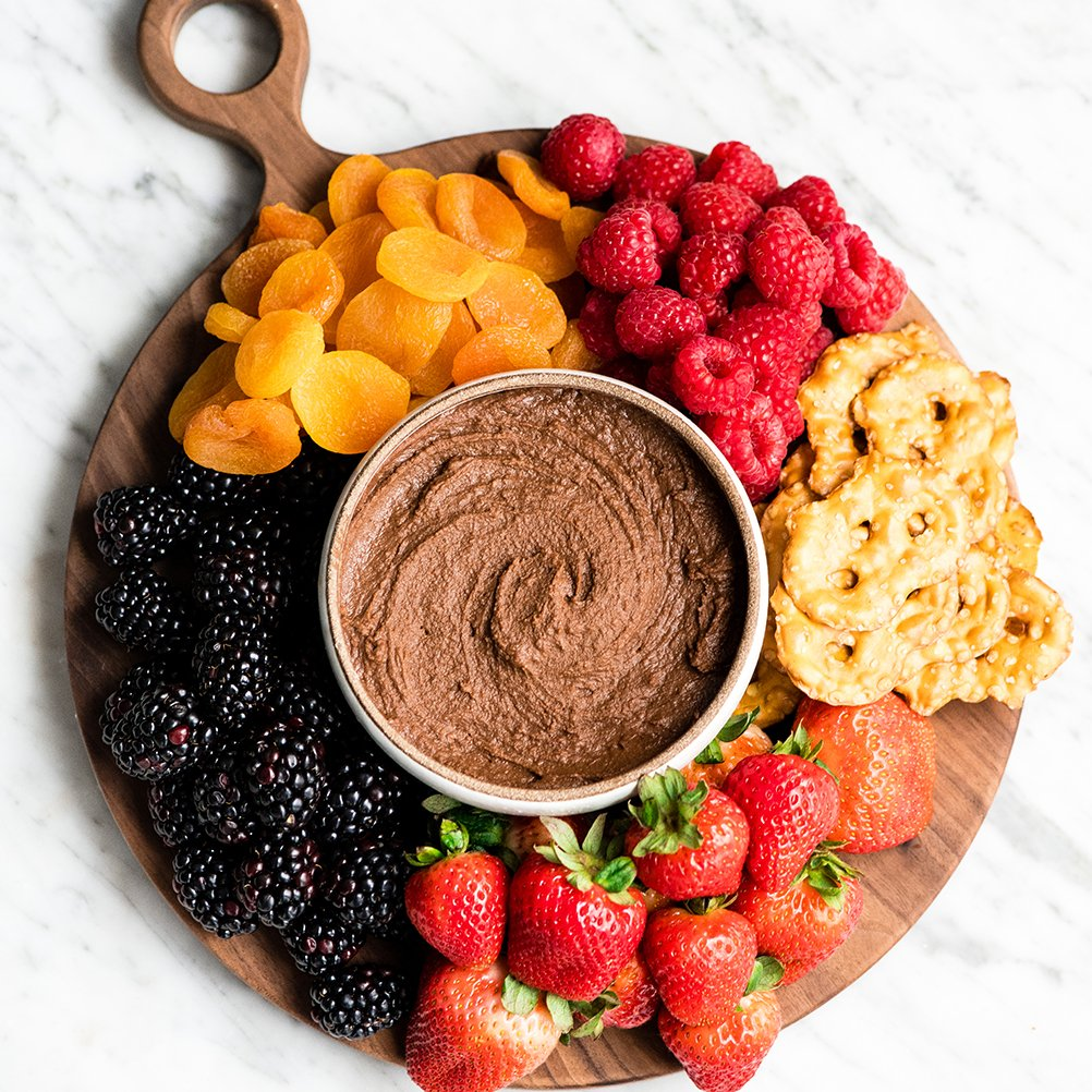 Overhead view of Chocolate Hummus in a bowl surrounded by fruits and pretzels to dip in it