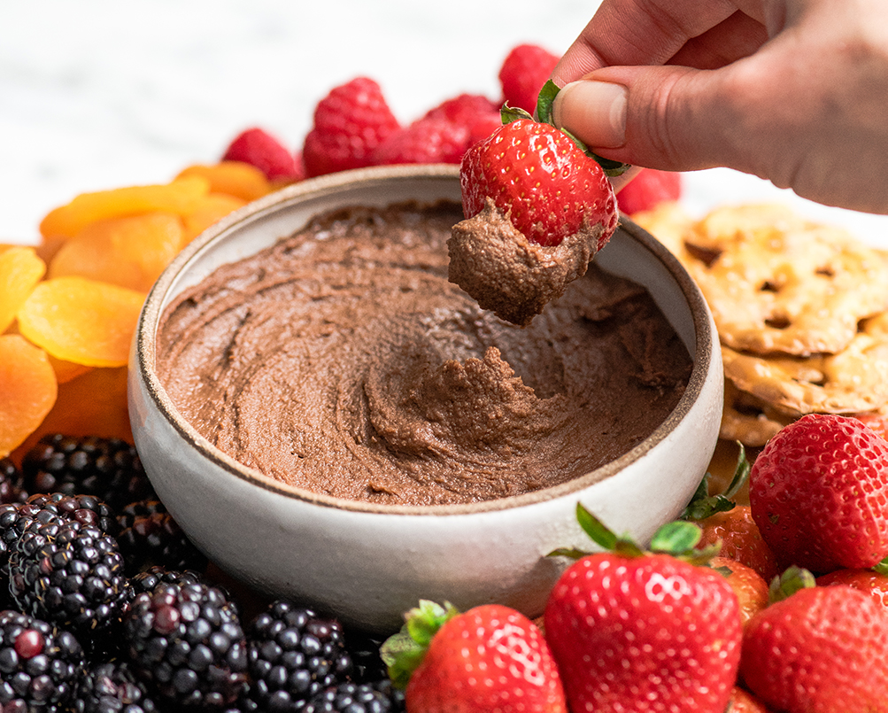 Front view of a hand dipping a strawberry into a bowl of Chocolate Hummus