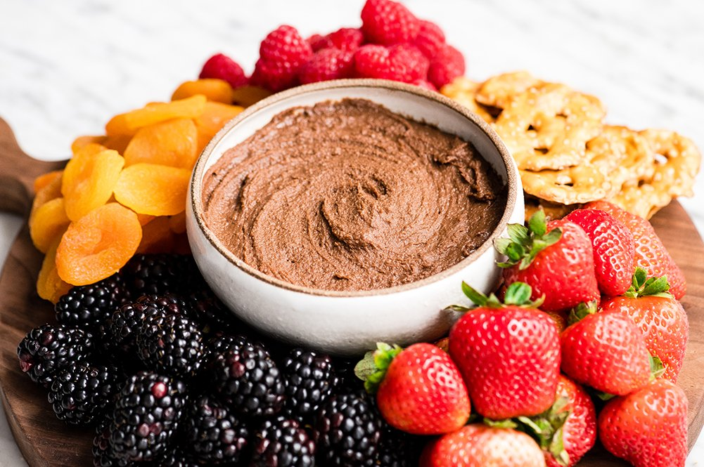 Front view of a bowl of chocolate hummus surrounded by fruits, dried fruits and pretzels