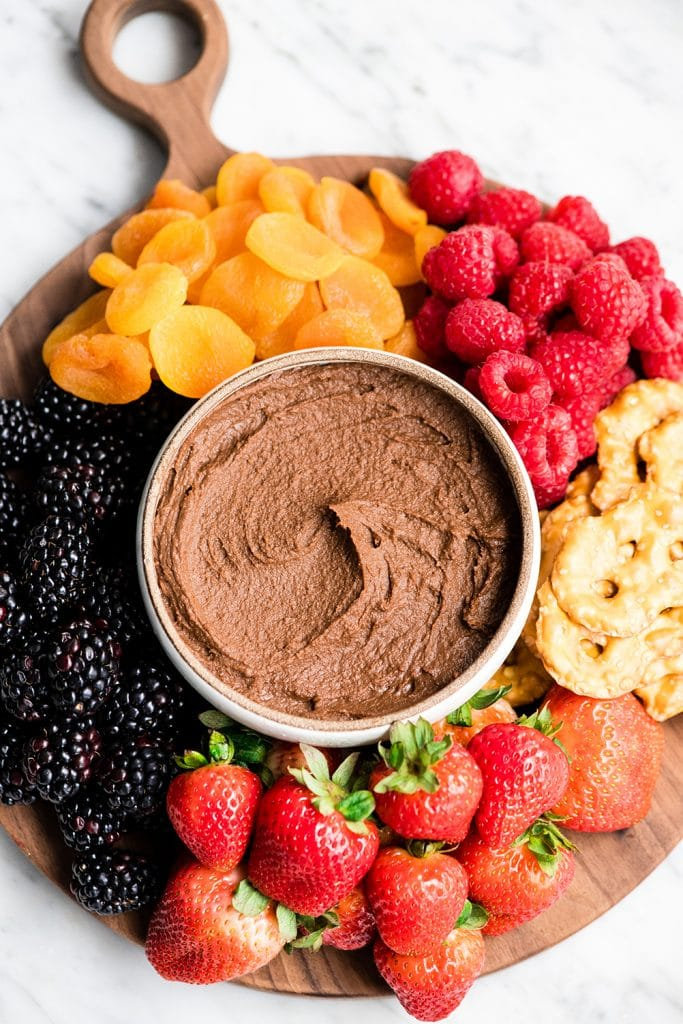 Overhead view of a cheese board loaded with fruit, pretzels, etc. with a bowl of Chocolate Hummus in the middle