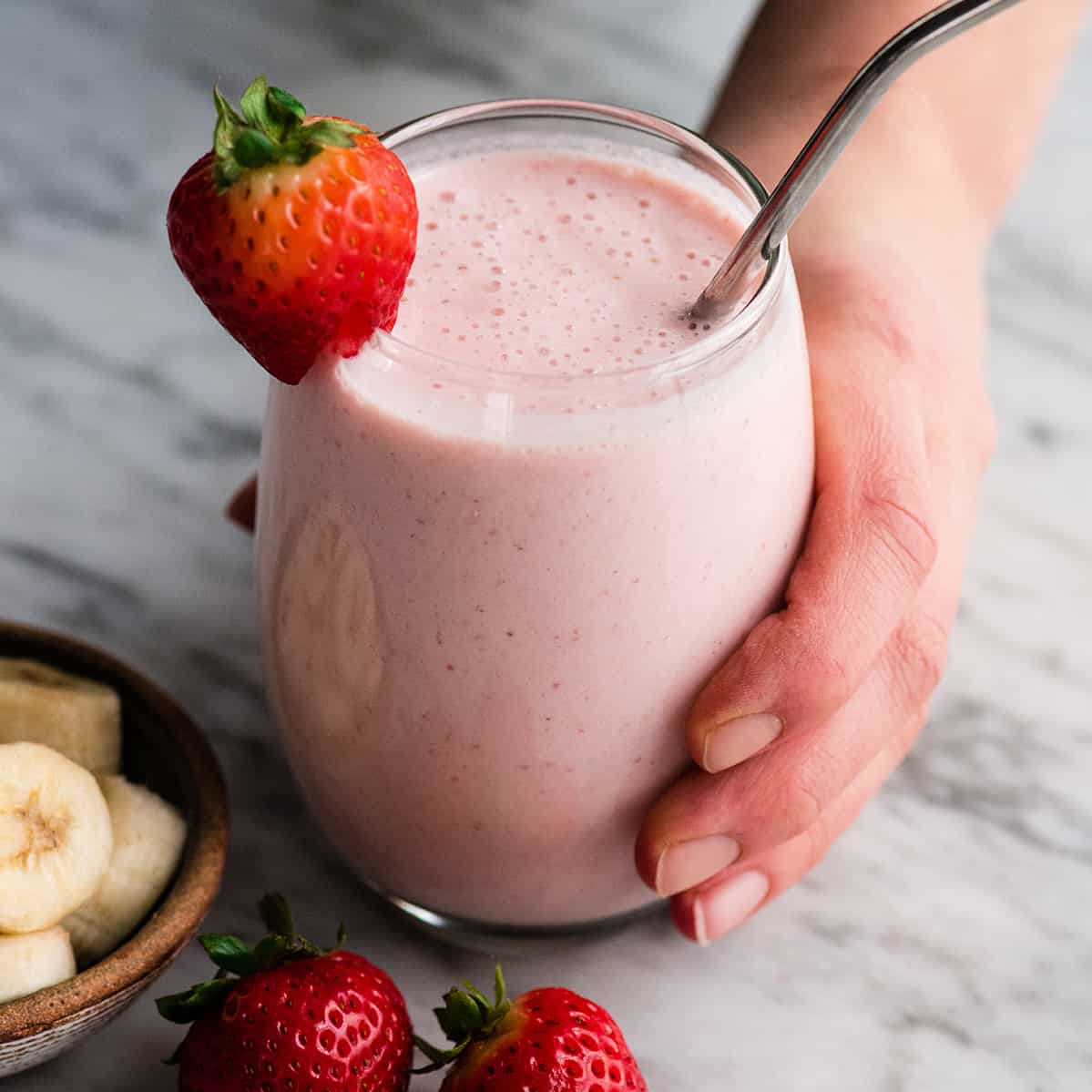 hand holding a glass filled with strawberry banana smoothie with a straw and strawberries.