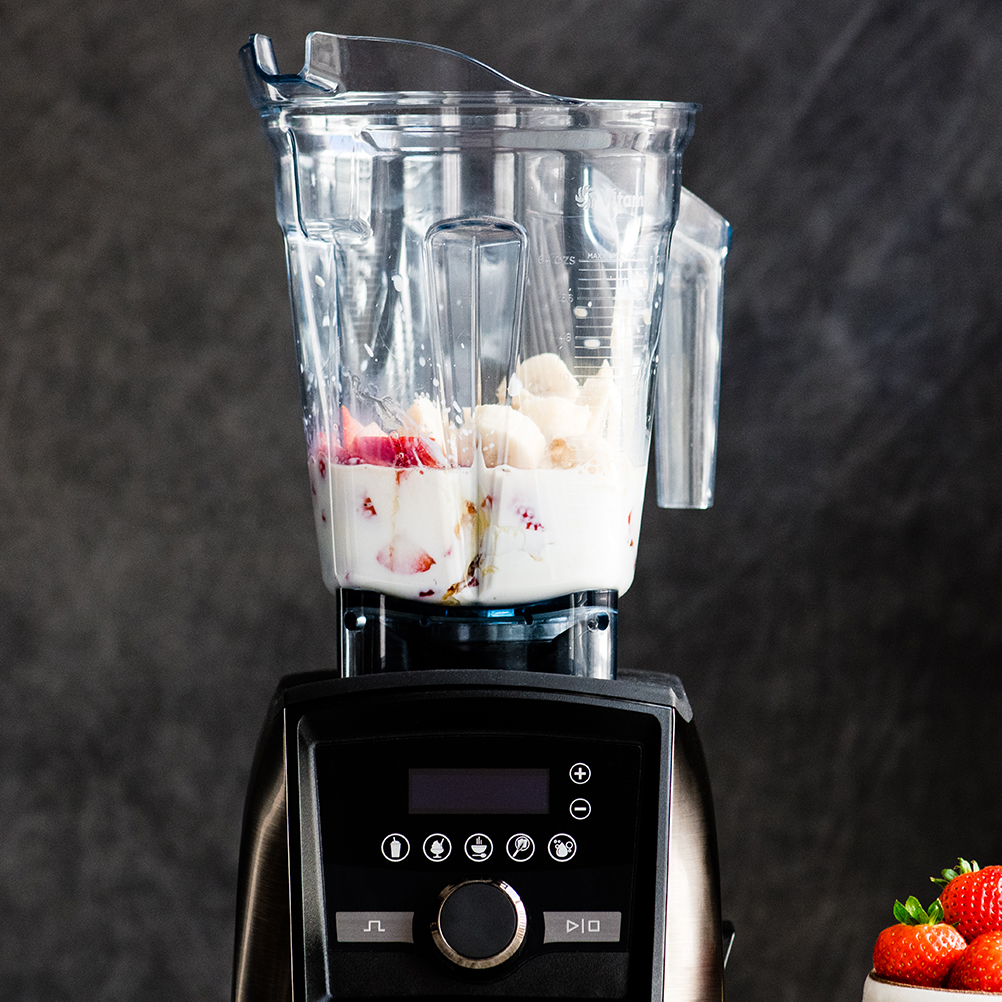 Front view of a Vitamix blender with the ingredients in it to make a Strawberry Banana Smoothie before blending