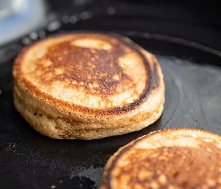 front view of a Greek Yogurt Pancake cooking in a cast iron skillet