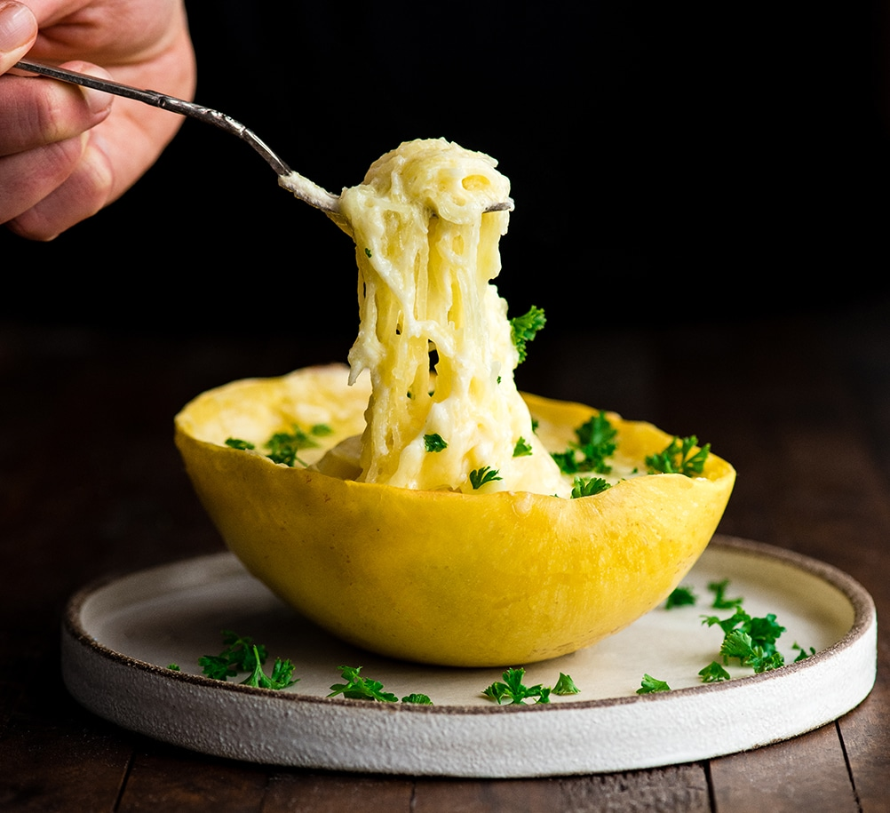 Front view of a hand holding a fork pulling a bite of Spaghetti Squash Mac and Cheese out of the shell