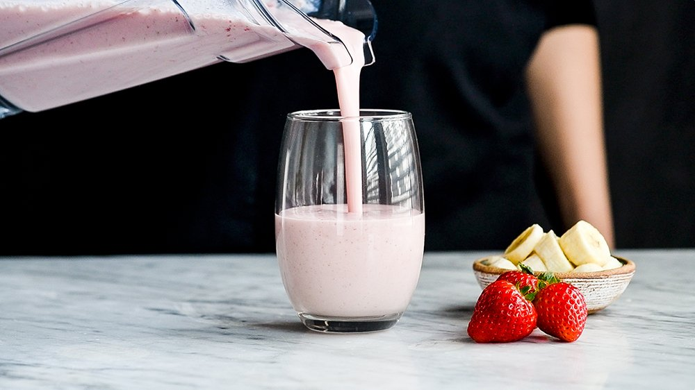 Front shot of a strawberry banana smoothie being poured out of the blender into a glass cup.