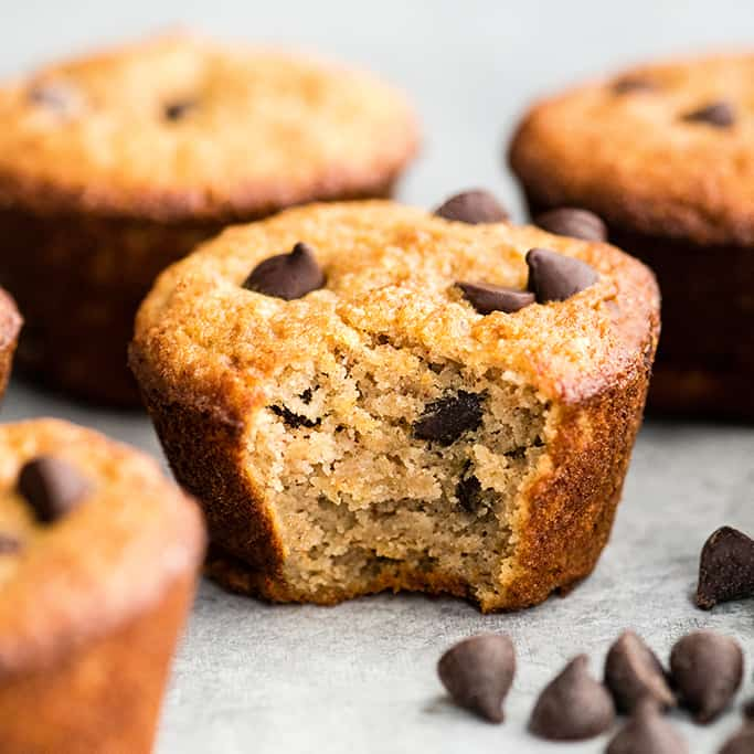 Front view of a healthy chocolate chip muffin with a bite taken out of it, with three other chocolate chip muffins in the background